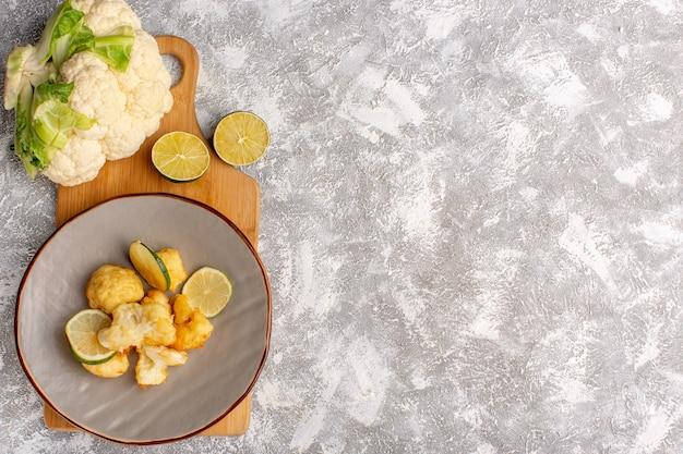 Vista superior de couve-flor fatiada cozida dentro do prato com limão na superfície branca