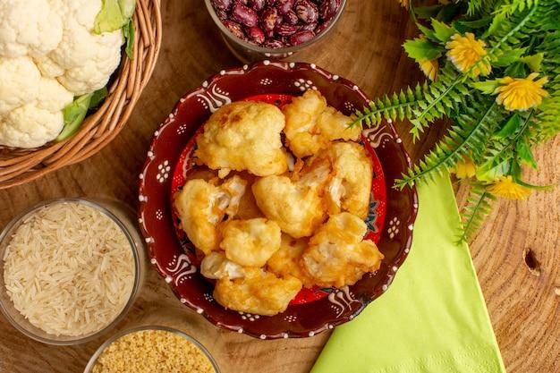 Vista superior de couve-flor fatiada cozida dentro do prato com verduras e arroz cru na superfície de madeira cremosa