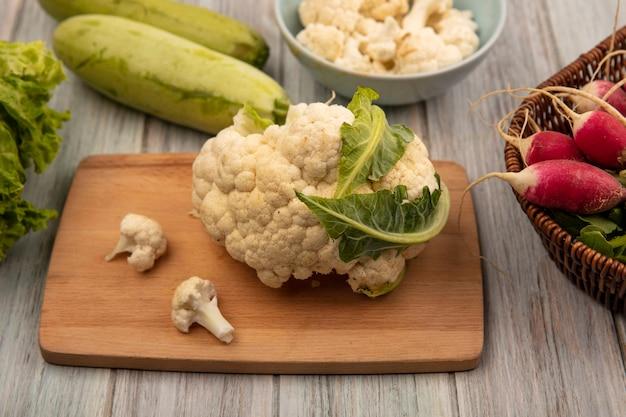 Vista superior de couve-flor rica em vitaminas em uma placa de cozinha de madeira com botões de couve-flor em uma tigela com rabanetes em um balde com abobrinhas isoladas em uma superfície de madeira cinza
