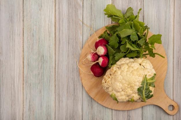 Vista superior de couve-flor saudável em uma placa de cozinha de madeira com rabanetes em uma superfície de madeira cinza com espaço de cópia
