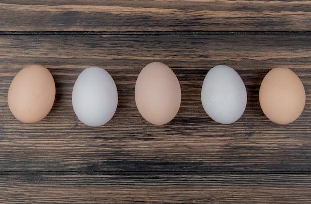 Vista superior de creme e ovos de galinha coloridos brancos sobre um fundo de madeira