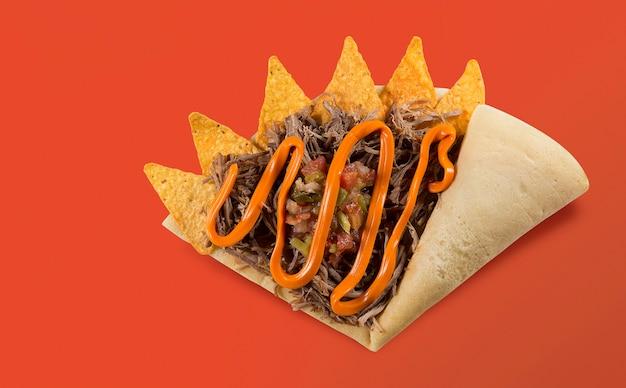 Vista superior de crepe ou panqueca fina com nachos, carne e queijo chedar em fundo de laranja.