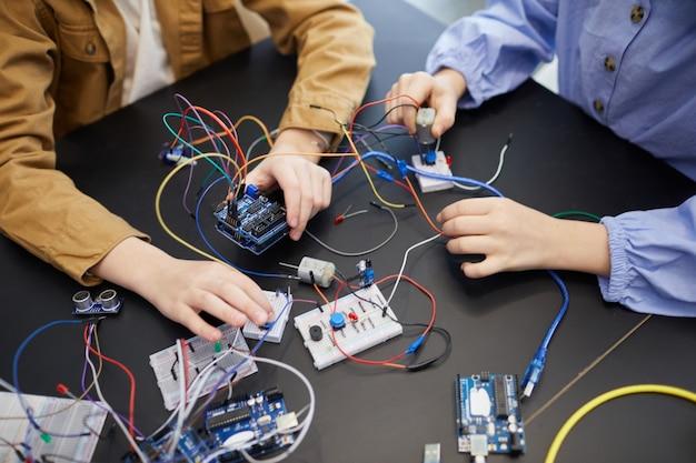 Vista superior de crianças irreconhecíveis construindo robôs e fazendo experiências com circuitos elétricos na aula de engenharia na escola, copie o espaço