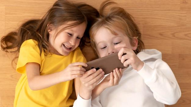 Vista superior de crianças usando smartphone juntos