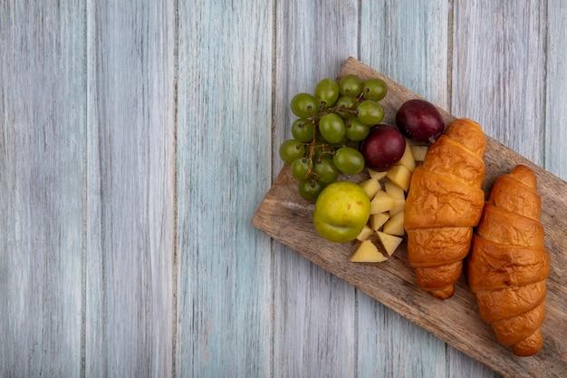 Vista superior de croissants com pluots de uva e queijo na tábua de corte em fundo de madeira com espaço de cópia