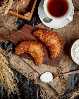 Vista superior de croissants de manteiga coloca na placa de madeira