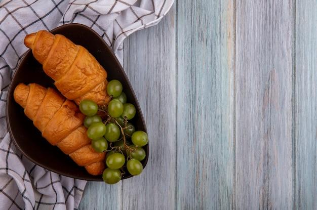 Vista superior de croissants e uva em uma tigela sobre pano xadrez em fundo de madeira com espaço de cópia