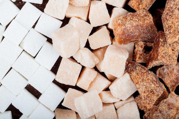 Vista superior de cubos de açúcar branco e marrom e pedaços de açúcar de palma espalhados no fundo escuro de madeira