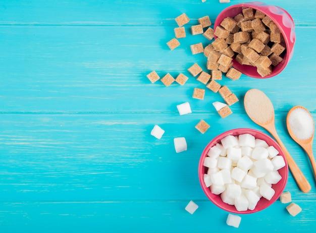 Vista superior de cubos de açúcar branco e marrom em taças sobre fundo azul de madeira, com espaço de cópia