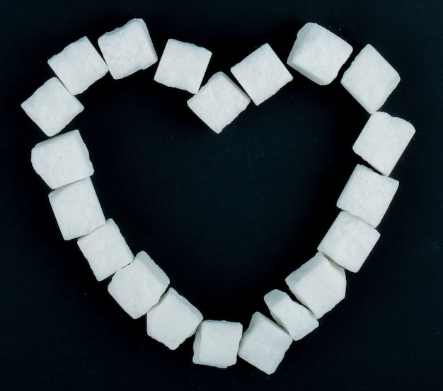 Vista superior de cubos de açúcar, dispostas em forma de coração em fundo preto