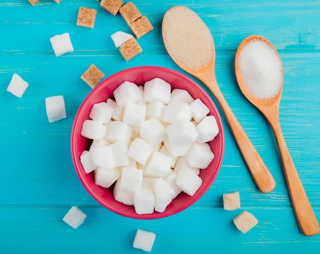 Vista superior de cubos de açúcar em uma tigela rosa e colheres de pau com açúcar sobre fundo azul