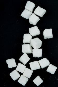 Vista superior de cubos de açúcar espalhados em fundo preto