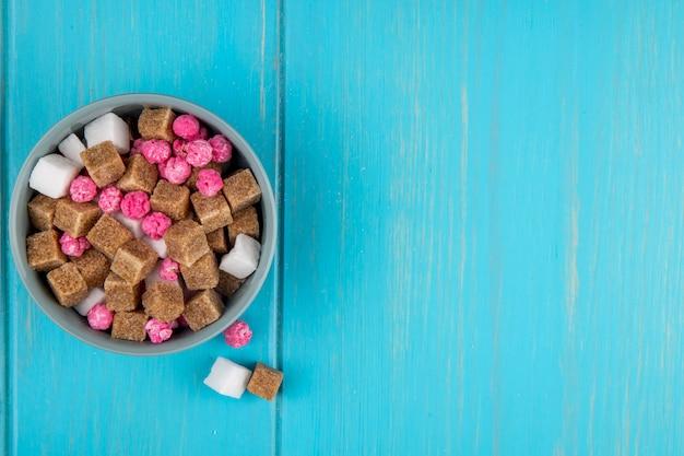 Vista superior de cubos de açúcar mascavo e doces cor de rosa em uma tigela em azul