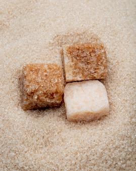 Vista superior de cubos de açúcar mascavo em fundo de açúcar granulado
