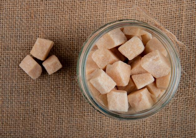 Vista superior de cubos de açúcar mascavo em uma jarra de vidro em fundo de textura de saco de carvão