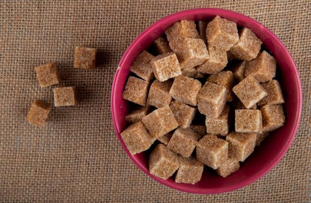 Vista superior de cubos de açúcar mascavo em uma tigela rosa em fundo de textura de saco de carvão