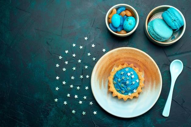 Vista superior de cupcake com decorações de estrelas ao lado de pratos de macarons e doces