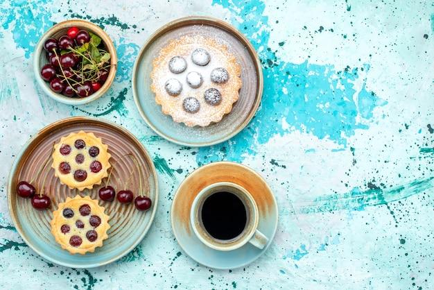 Vista superior de cupcakes com cerejas ácidas e americano quente
