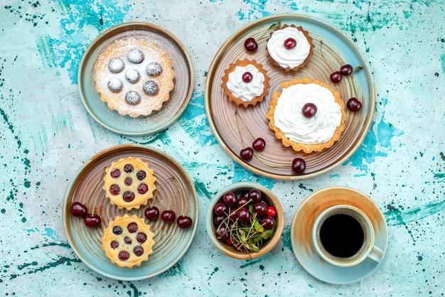 Vista superior de cupcakes com cerejas em pó e creme ao lado do americano