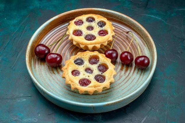 Vista superior de cupcakes com cerejas frescas ao lado de um cacho de cerejas na mesa azul
