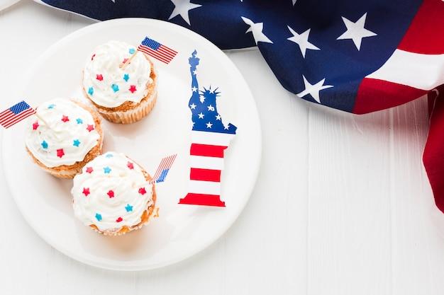 Vista superior de cupcakes no prato com a estátua da liberdade e bandeiras americanas