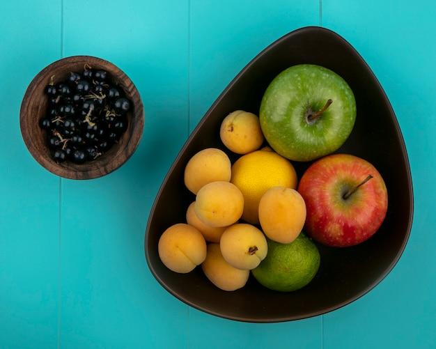 Vista superior de damascos com maçãs e limão com groselha preta em uma tigela sobre uma superfície azul clara
