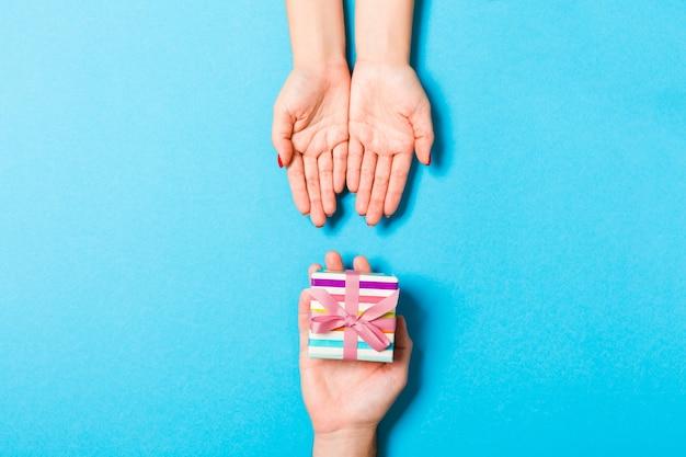 Vista superior de dar e receber um presente em fundo colorido. um homem e uma mulher segurando presente nas mãos