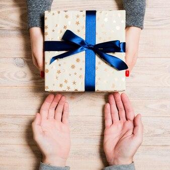 Vista superior de dar e receber um presente na mesa de madeira. um homem e uma mulher segurando presente nas mãos. feche acima do conceito festivo