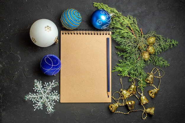 Vista superior de decorações de ano novo e caderno com caneta em fundo preto