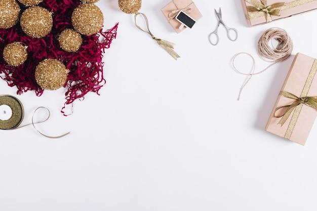 Vista superior de decorações de natal, caixas com presentes, tesoura e fitas em uma mesa branca