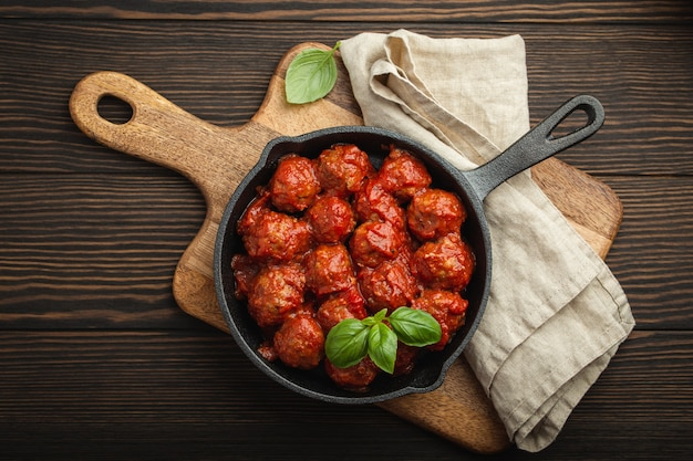 Vista superior de deliciosas almôndegas com molho de tomate e manjericão fresco em panela vintage rústica de ferro fundido, servido na tábua, fundo de madeira. saborosas almôndegas caseiras