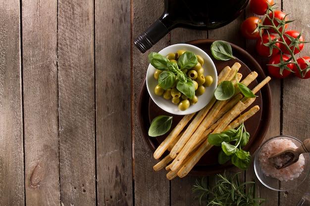 Vista superior de deliciosas azeitonas com outros produtos na superfície de madeira