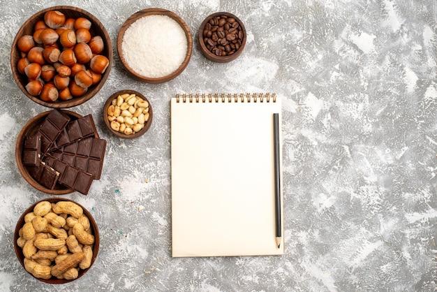 Vista superior de deliciosas barras de chocolate com avelãs e amendoim na superfície branca