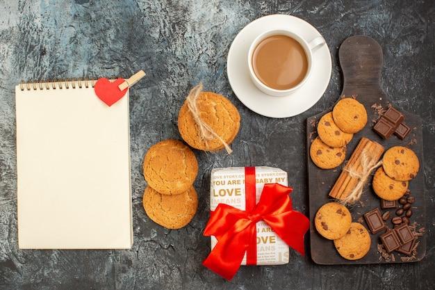Vista superior de deliciosas barras de chocolate para biscoitos e uma caixa de presente para caderno espiral com uma xícara de café na superfície escura e gelada