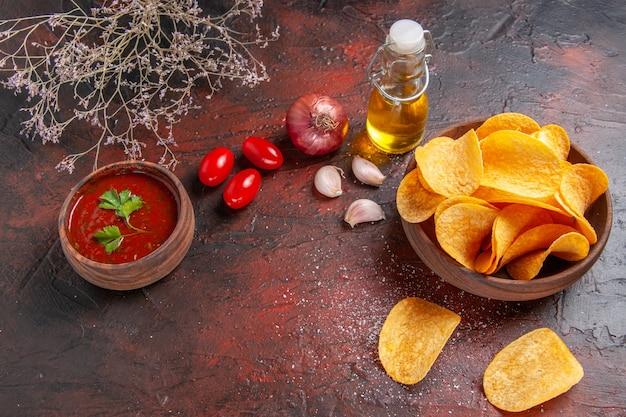 Vista superior de deliciosas batatas fritas caseiras crocantes, dentro e fora de uma garrafa de óleo de maconha marrom, tomate, alho, cebola, em fundo escuro