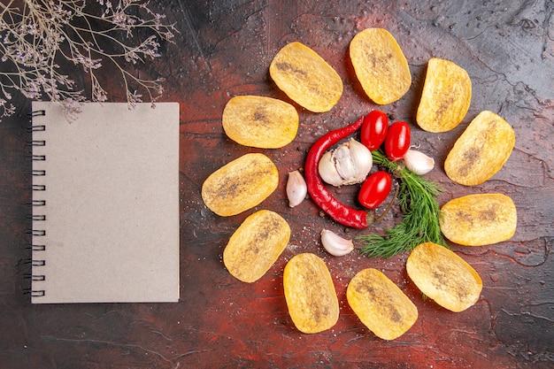 Vista superior de deliciosas batatas fritas caseiras crocantes pimenta vermelha alho verde tomate e caderno na mesa escura