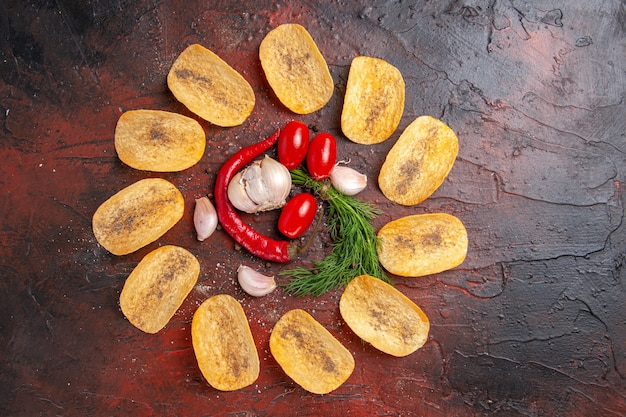 Vista superior de deliciosas batatas fritas caseiras crocantes pimenta vermelha alho verde tomate na mesa escura