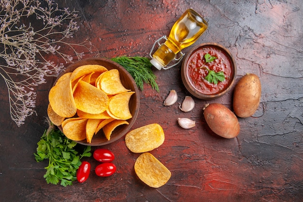 Vista superior de deliciosas batatas fritas caseiras em uma tigela marrom pequena garrafa de óleo de batata verde tomate alho e ketchup em fundo escuro