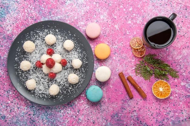 Vista superior de deliciosas bolas de doces de coco com macarons franceses na superfície rosa