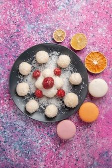 Vista superior de deliciosas bolas de doces de coco com macarons na superfície rosa