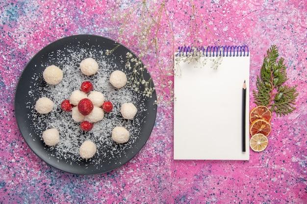 Vista superior de deliciosas bolas de doces de coco na superfície rosa claro