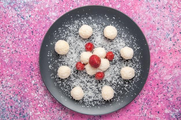 Vista superior de deliciosas bolas de doces de coco na superfície rosa