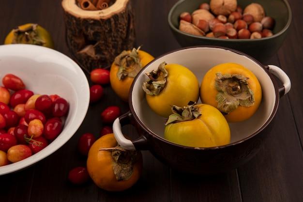 Vista superior de deliciosas cerejas da cornalina em uma tigela branca com frutas de caqui em uma tigela com nozes em uma tigela com paus de canela em uma jarra de madeira sobre uma superfície de madeira