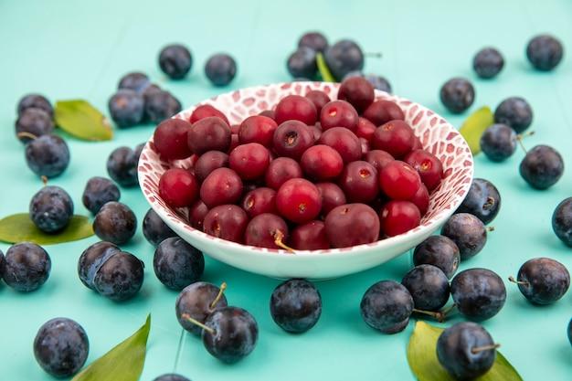 Vista superior de deliciosas cerejas em uma tigela com pequenas abrunhas roxas escuras em um fundo azul