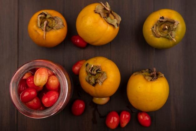 Vista superior de deliciosas cerejas vermelhas da cornalina em uma jarra de vidro com frutas caqui isoladas em uma superfície de madeira