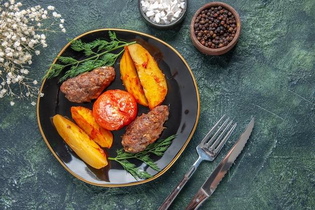 Vista superior de deliciosas costeletas de carne assadas com batatas e tomates em uma placa preta talheres com especiarias de flores brancas sobre fundo verde preto cores misturadas