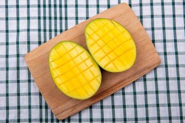 Vista superior de deliciosas fatias de manga frescas exóticas na placa de cozinha de madeira em uma toalha de mesa xadrez