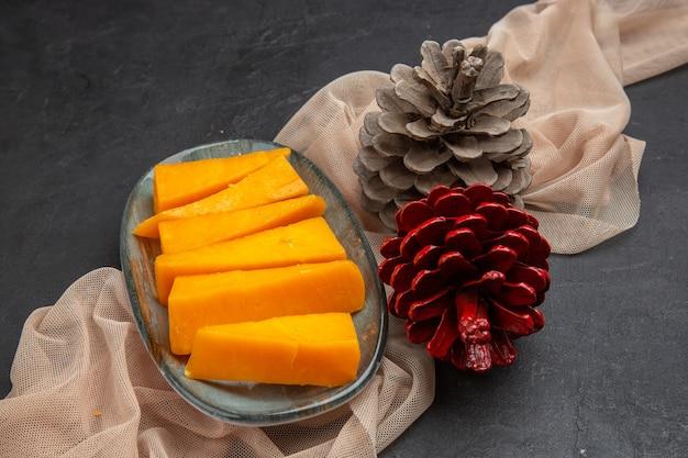 Vista superior de deliciosas fatias de queijo e cones de coníferas em uma toalha em um fundo preto