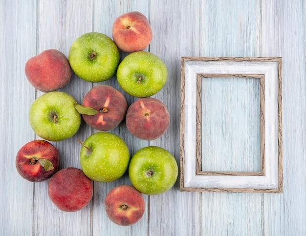 Vista superior de deliciosas frutas frescas coloridas, como maçã e pêssegos em madeira cinza com espaço de cópia