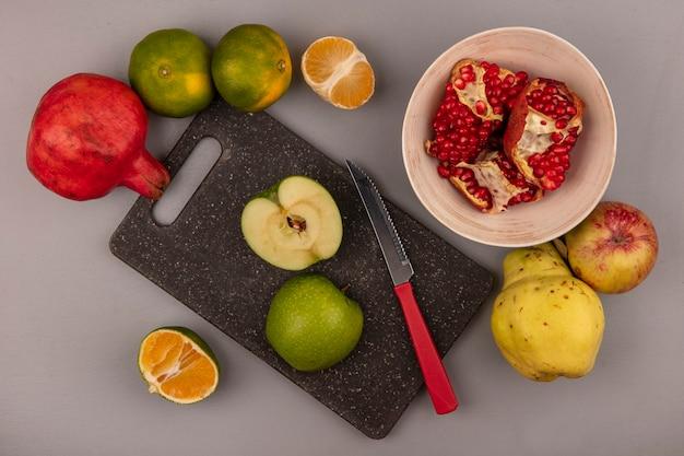 Vista superior de deliciosas maçãs fatiadas em uma placa de cozinha preta com faca com romãs em uma tigela com maçã de marmelo e tangerinas isoladas